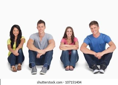 A smiling group looking at the camera with their knees up and their arms on them