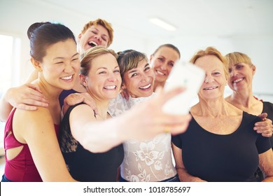 Smiling group of mature women standing arm in arm together taking a selfie with their dance teacher during ballet class