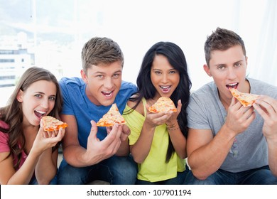 A smiling group with mouths open about to eat pizza as they look at the camera