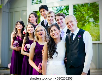 Smiling group of multiethnic wedding party together outside