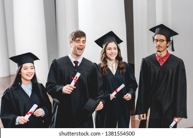 smiling group on students in graduation gowns holding diplomas