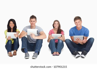 A smiling group of people sitting on the ground beside each other while using tablets and looking at the camera