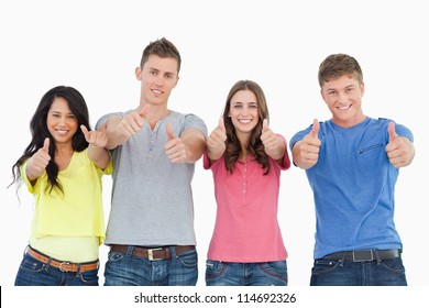 A smiling group of people stand beside each other looking at the camera as they all give thumbs up