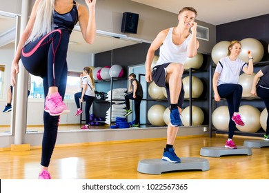 Smiling group raising legs on step platforms at fitness gym