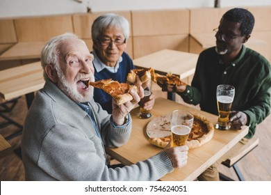 smiling group of senior friends drinking beer with pizza at cafe