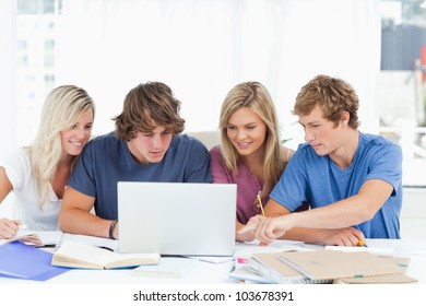 A smiling group of students use a laptop while working together