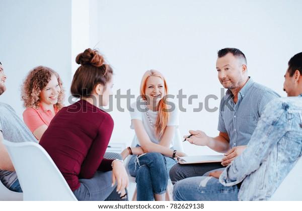 Lächelnde Gruppe von Teenagern während eines Treffens mit Persönlichkeitstrainer hilft ihnen, Selbstvertrauen zu gewinnen