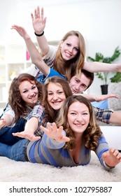 Smiling group of teenagers friends having fun on floor