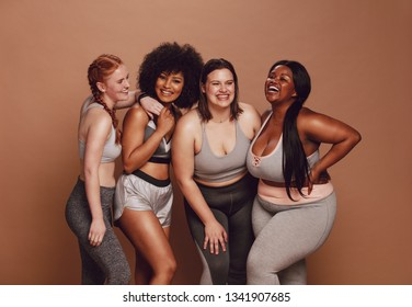 Smiling group of women in different size standing together in sportswear against brown background. Diverse group women looking at camera and laughing.
