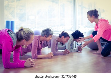 Smiling group of women exercising on floor in fitness studio