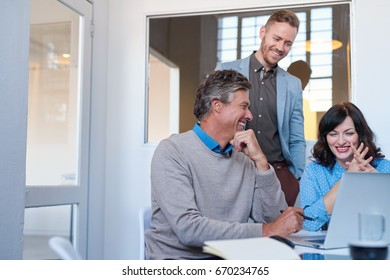 Smiling group of young businesspeople sitting at a table laughing while working together on a laptop in a modern office