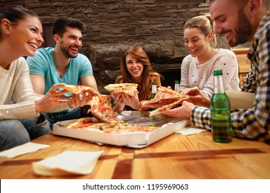 Smiling group of young people eating's big pizza together
