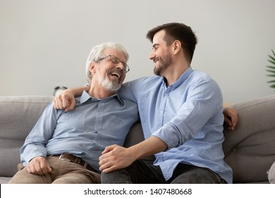 Smiling grown son sit on couch relax with senior dad talk sharing thoughts looking in eyes, happy millennial man rest on sofa speak with elderly father enjoy leisure family weekend at home