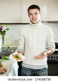 smiling guy  with cooked fish steak on plate at home  kitchen