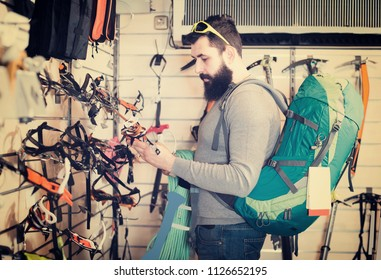 Smiling guy deciding on climbing equipment in sports equipment store