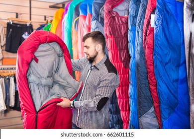 Smiling guy deciding on new sleeping bag at a sports equipment store