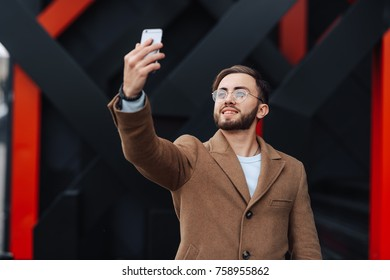 Smiling guy in glasses and brown coat using his mobile smartphone on a red and black wall background