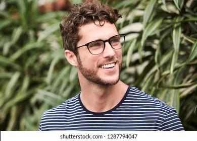 Hombre sonriente con gafas, mirando lejos