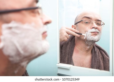 Smiling guy in glasses shaving his beard with disposable razor