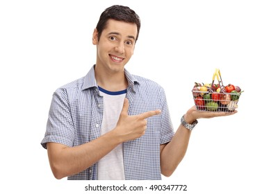 Smiling guy holding a small shopping basket full of fruits and vegetables and pointing isolated on white background
