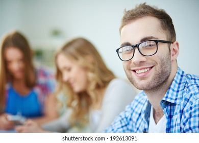 Smiling guy looking at camera with his groupmates on background