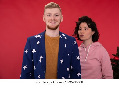 Smiling guy looking at camera, wild hair girl looking away. casual dressed attractive caucasian couple posing on red backdrop with different emotions near christmas tree. Sexual disharmony concept