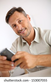 Smiling guy sending message with smartphone