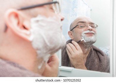 Smiling guy shaving his beard with disposable razor and looking at mirror
