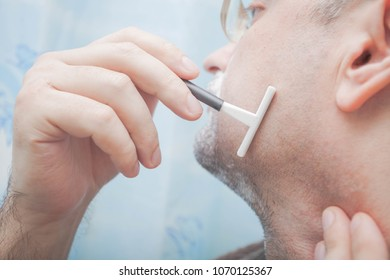 Smiling guy shaving his beard with disposable razor