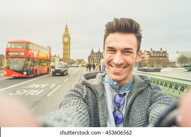 Smiling guy take selfie photo during travel in London, England. Traveler man in front of Big Ben Tower taking memory pic with iconic england red bus. Happy people concept wandering around the world.