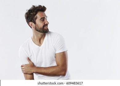 Smiling guy in white t-shirt, looking away