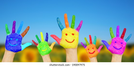 Smiling hands on summer background. Children's hands in colorful paint with smiles. Summer holidays and fun games concept.