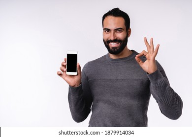 Smiling handsome 25s Middle Eastern man showing okay sign holding smartphone isolated over white background