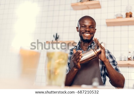 smiling handsome african american bartender making cocktail in shaker on bar counter