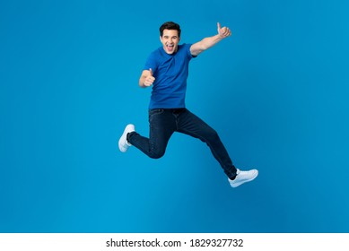 Smiling handsome American man joyfully jumping and doing double thumbs up gesture isolated on blue studio background