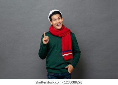 Smiling handsome Asian man wearing  Christmas theme clothes looking at empty space aside and thinking with hand pointing up, studio shot isolated on gray background
