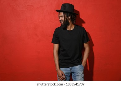 Smiling handsome attractive young african american man guy with dreadlocks 20s wearing black casual t-shirt hat posing looking aside isolated on bright red color wall background studio portrait
