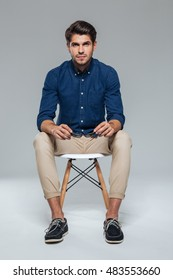 Smiling handsome brunette man in blue shirt sitting on the chair and holding sunglasses