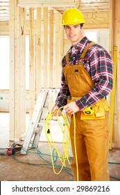 Smiling handsome builder in yellow uniform.