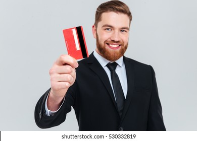 Smiling handsome business man in black suit holding credit card in hand and looking at camera. Isolated gray background