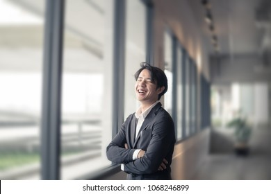 A smiling handsome business man, is standing near the window in acting like cross his arms. He is smart and clever manager, and sometimes he is a model for portrait photograph, with blurry background.