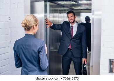 smiling handsome businessman holding elevator door for woman