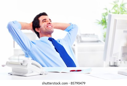 Smiling handsome businessman relaxing  in a modern office.