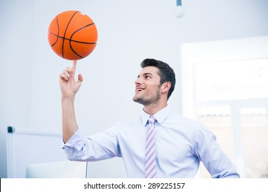 Smiling handsome businessman spining ball in office