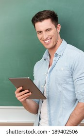 Smiling handsome casual young man standing in front of a clean chalkboard holding a tablet computer in his hands