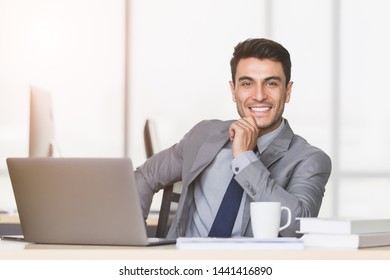 Smiling handsome Caucasian businessman touch his wrist, there is notebook computer on table in modern office.