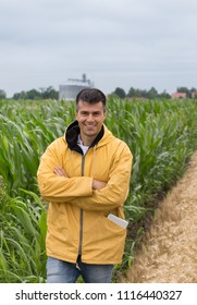 Smiling handsome farmer with crossed arms standing in front of corn field and silos in background
