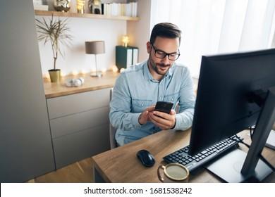 Lächelnder gut aussehender Freiberufler, der aus der Ferne von zu Hause aus arbeitet. Er telefoniert.