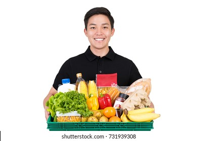 Smiling handsome grocery store Asian delivery man wearing a black polo-shirt holding food basket isolated on white background
