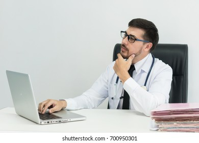Smiling handsome male accounting office worker sitting at desk massaging his chin  while thinking  look at laptop computer screen.